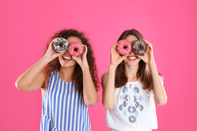 Beautiful young women with donuts on pink background