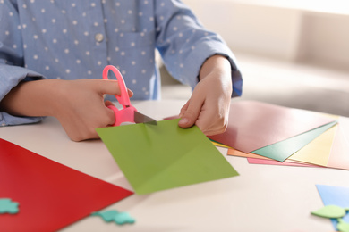 Little girl making greeting card at table indoors, closeup. Creative hobby