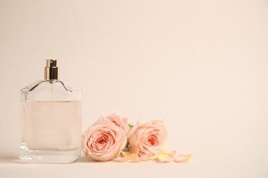 Bottle of perfume with roses on beige background, space for text