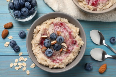 Tasty oatmeal porridge with toppings served on light blue wooden table, flat lay