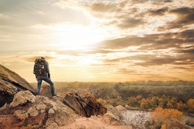 Hiker with travel backpack enjoying beautiful view near mountain river, back view
