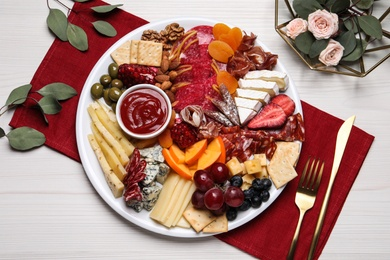 Plate of different appetizers with sauce served on white wooden table, flat lay