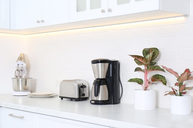 Modern toaster and household appliances on counter in kitchen