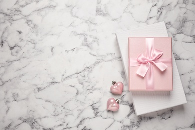 Beautiful gift boxes and festive decor on white marble table, flat lay. Space for text