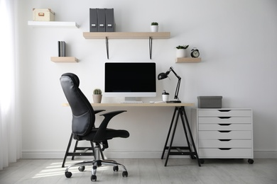 Comfortable office chair near table with modern computer