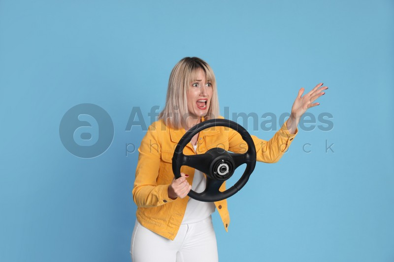 Emotional woman with steering wheel on light blue background