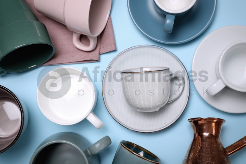 Different cups and jezve on light blue background, flat lay