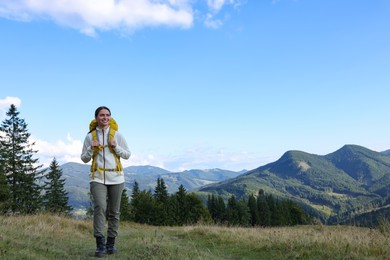 Tourist with backpack hiking through mountains, space for text