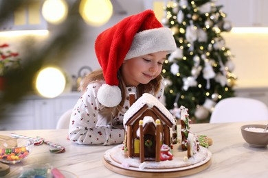 Cute little girl decorating gingerbread house at table indoors