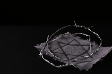 Fabric with star of David and barbed wire on black background, space for text. Holocaust memory day