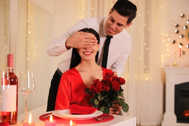 Man presenting roses to his beloved woman in restaurant. Romantic Valentine's day dinner