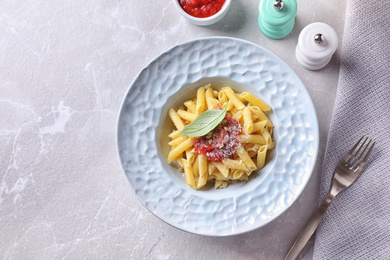 Delicious pasta with tomato sauce served on light table, flat lay