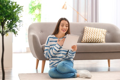 Woman using tablet for video chat in living room