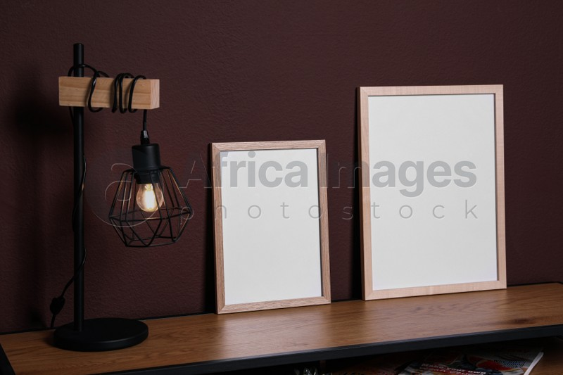 Empty frames and stylish lamp on wooden table near brown wall. Mockup for design