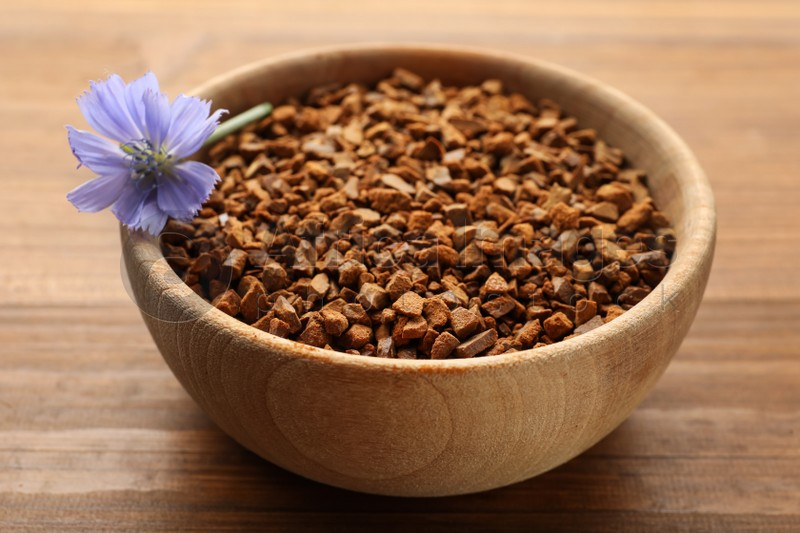 Bowl of chicory granules with flower on wooden table