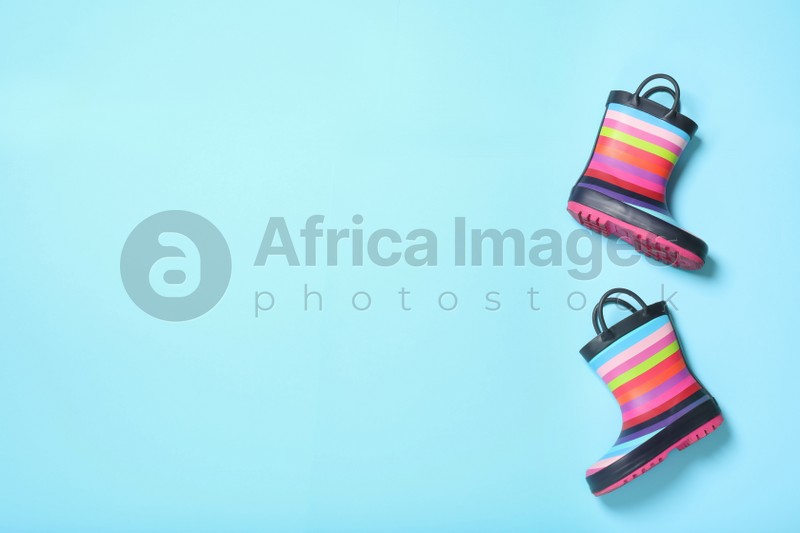Striped rubber boots on light blue background, top view. Space for text