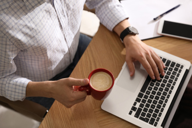 Man with cup of coffee and laptop at workplace, closeup