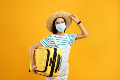 Female tourist in medical mask with suitcase on yellow background. Travelling during coronavirus pandemic