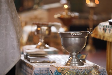 Silver vessel with holy water on stand in church. Baptism ceremony