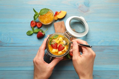 Woman eating delicious mango jelly with fresh fruits  at light blue wooden table, top view