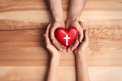 Couple holding heart with cross symbol on wooden background, top view. Christian religion