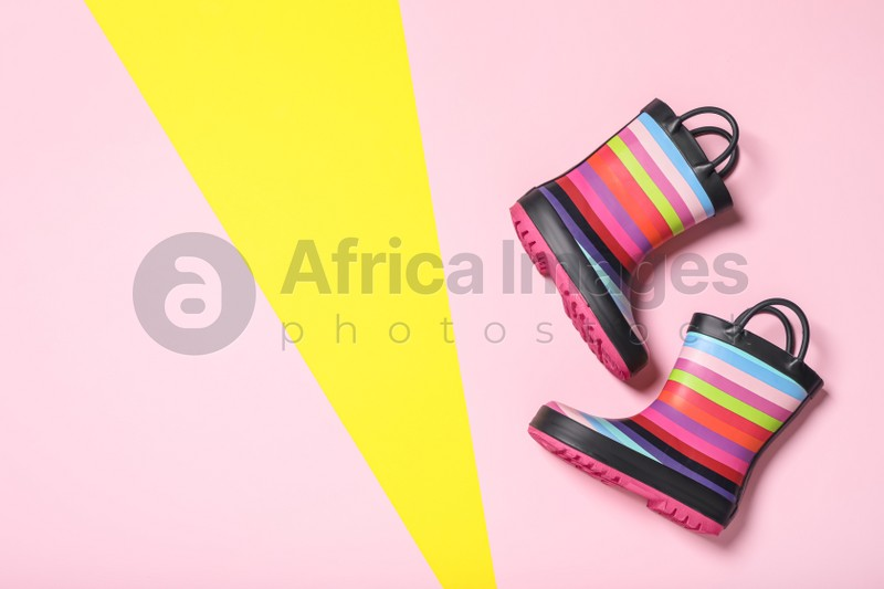 Pair of striped rubber boots on color background, top view. Space for text