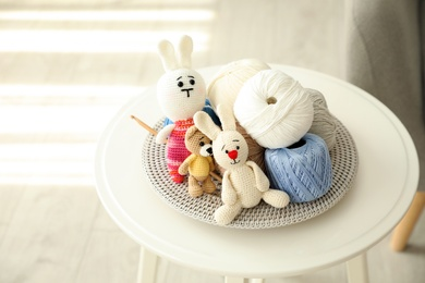 Crocheted toys and clews on white table. Engaging in hobby