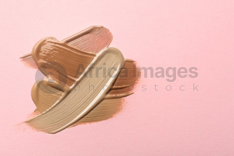 Different shades of liquid foundation on pink background, top view. Space for text