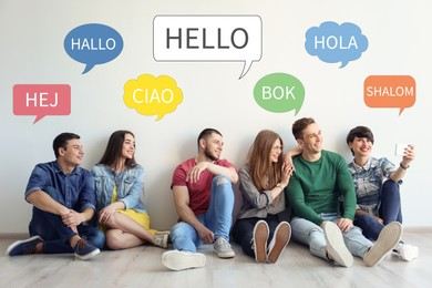 Happy people sitting near light wall and illustration of speech bubbles with word Hello written in different languages