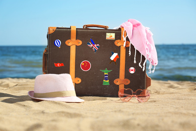 Retro suitcase with travel stickers on beach