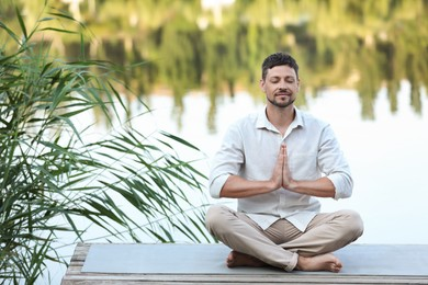 Man meditating on wooden pier near river. Space for text