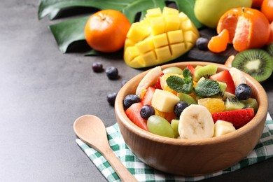 Delicious fresh fruit salad on grey table, space for text