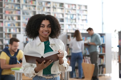 Young African-American woman with book in library
