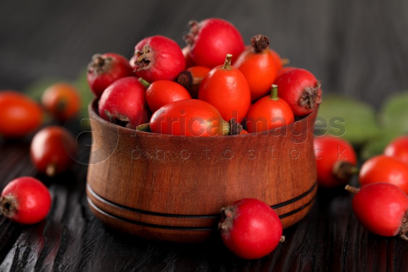 Ripe rose hip berries with green leaves on black wooden table, closeup