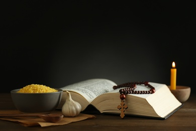 Fasting meals, Bible, rosary beads and candle on wooden table. Lent season