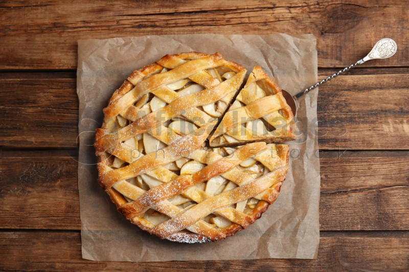 Delicious traditional apple pie on wooden table, top view