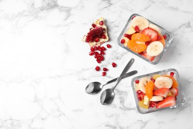 Delicious fresh fruit salad in bowls on white marble table, flat lay. Space for text