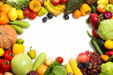 Frame of assorted fresh organic fruits and vegetables on white background, top view. Space for text