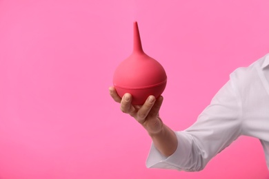 Woman holding enema on pink background, closeup