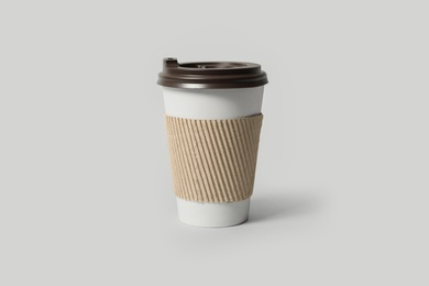Takeaway paper coffee cup with cardboard sleeve on light grey background