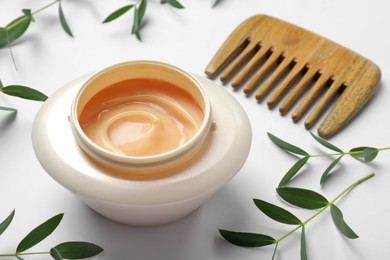 Jar of hair care cosmetic product, wooden comb and green leaves on white background, closeup