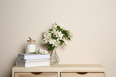 Bouquet of beautiful jasmine flowers in glass vase, books and candle on wooden commode near beige wall indoors