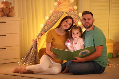 Family with flashlight reading book at home