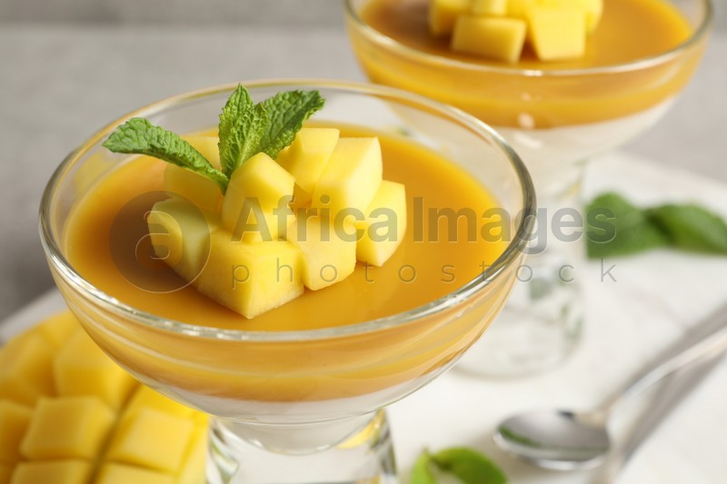 Delicious panna cotta with mango coulis, fresh fruit pieces and mint in dessert bowl, closeup