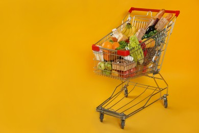 Shopping cart full of groceries on yellow background. Space for text