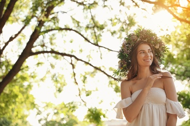 Young woman wearing wreath made of beautiful flowers outdoors on sunny day