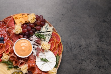 Wooden plate with different delicious snacks on grey table, top view. Space for text