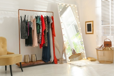Rack with different stylish women's clothes and mirror indoors