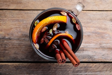 Aromatic mulled wine on wooden table, top view