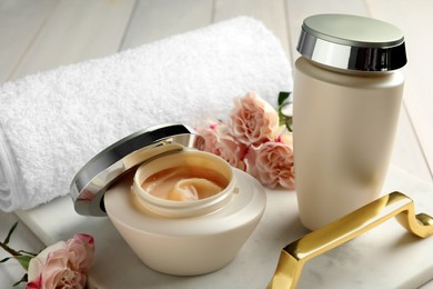 Hair care cosmetic products, beautiful flowers and towel on white table